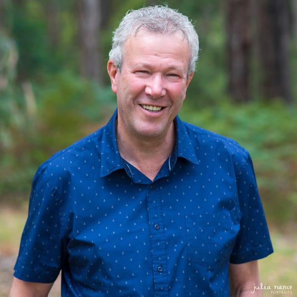 Smiling personal branding portrait of man outside wearing a blue shirt.