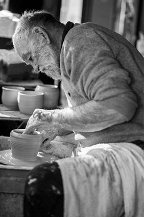 Portrait of professional potter Graeme Anderson in Lightning Ridge while on his pottery wheel