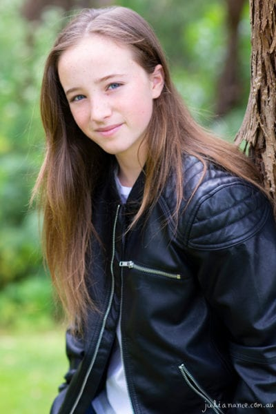 Melbourne actor headshot of young girl leaning against a tree in a denim jacket