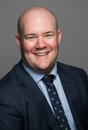 Melbourne corporate headshot of man smiling on grey background wearing a suit and tie for a LinkedIn headshot