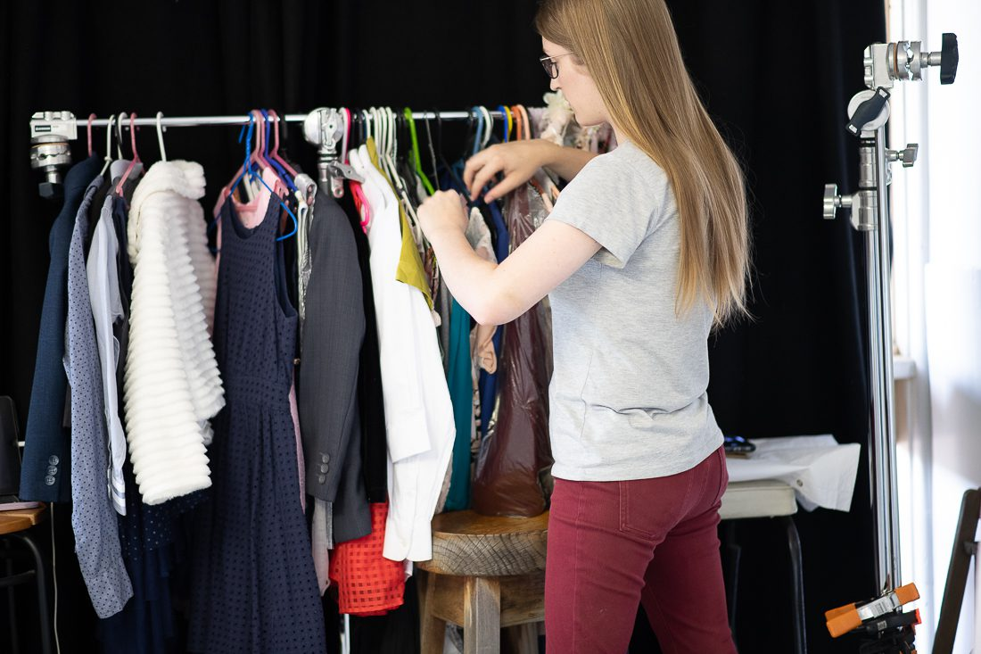 Julia Nance in her professional headshot photography studio, looking at clothing rack