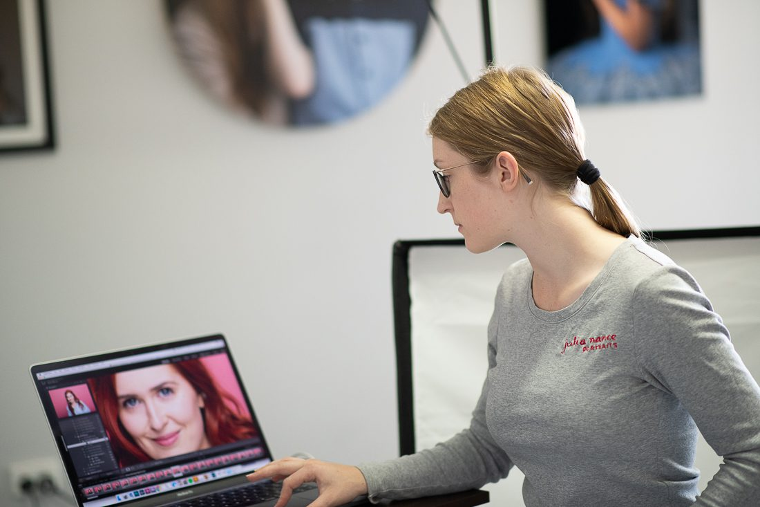 Julia Nance in her professional headshot photography studio, looking at laptop