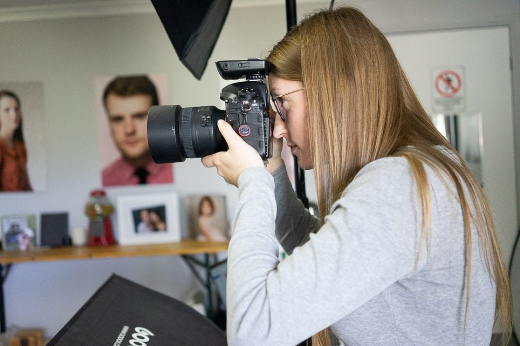 Julia Nance in her professional headshot photography studio, looking through her camera