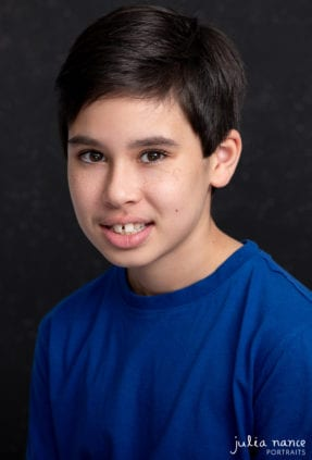 Child actor headshot of young boy in a studio environment, with black background.